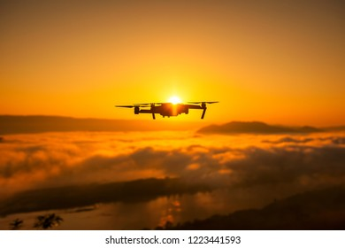 Silhouette drone on sunset, Drone quad copter with digital camera at sunset ready to fly for surveillance.