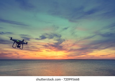Silhouette of Drone Quad copter flying in sky. Aerial panoramic view of sunset over ocean. Dramatic picturesque evening scene. Ocean and colorful cloudy sky in the background. Travel background
