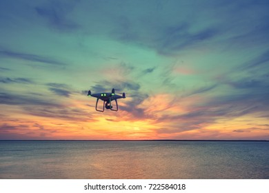 Silhouette of Drone Quad copter flying in sky. Aerial panoramic view of sunset over ocean. Dramatic picturesque evening scene. Colorful cloudy sky in the background. Vehicle at sundown and copy space