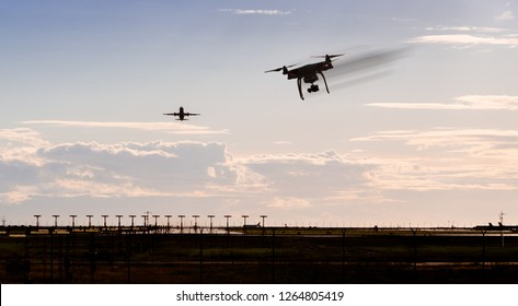 A silhouette of a drone rapidly moving towards an departing aircraft near a airport.