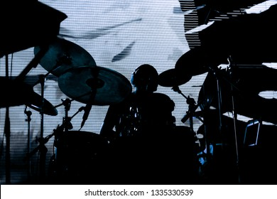 silhouette of a drummer behind the drum set on stage during a concert on the background a screen