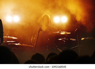 Silhouette of the drummer musician sitting behind the drum set in the bright background light of the spotlights. Rock concert. Blurred. Horns. That rocks. Party in a club