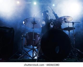 Silhouette drummer on stage. Dark background, smoke spotlights