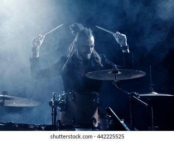 Silhouette drummer on stage. Dark background, smoke spotlights