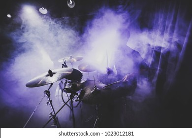silhouette of drummer / percussion / cymbal /drum player playing on drums on a concert . Club lights, fog, smoke, artist show.
