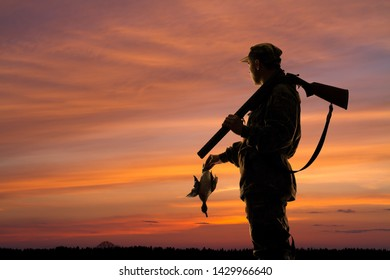 silhouette of the duck hunter with downed duck on the sunset background