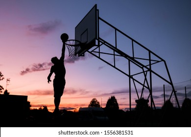 silhouette dunking man at sunset. basketball player scoring