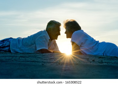 Silhouette of an elderly couple in love at sunset