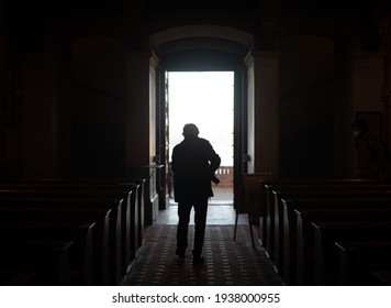 Silhouette of an elderly man standing in a doorway. A light and dark photo in low key. Stock photography.