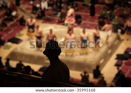Silhouette of an elderly man watching sumo wrestlers standing in a ceremonial ring