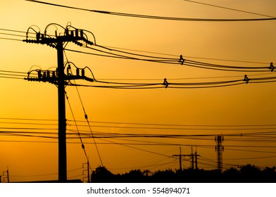 Silhouette of electric pole with cable on dramatic sunset sky, horizontal frame