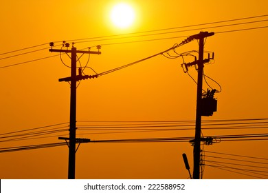 Silhouette of electric pole power lines and wires in sunset sky