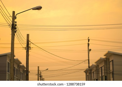 silhouette electric pole with townhome and sunset light