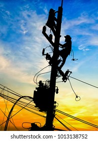 Silhouette Electrical engineers working on electricity pylon high tension power line repairs and maintenance with blurred background beautiful twilight sky