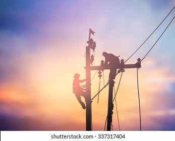 Silhouette electrical workers are installing high voltage systems over blur night city