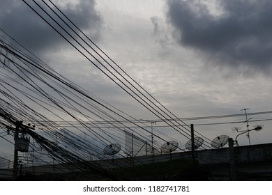Silhouette of electricity cables and satellite dishes