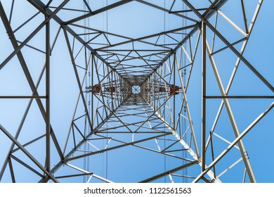 silhouette of electricity pylon with blue sky, upward view