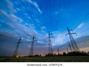 Silhouette of electricity pylons and high-voltage power lines on the wheat field at dusk. Four electricity pylons in a row on the background of beautiful sky. Electrical Power Grid at twilight.