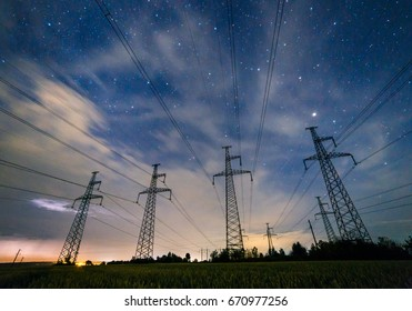 Silhouette of electricity pylons and high-voltage power lines on the wheat field at night. Four electricity pylons on the background of sky with clouds at night. Thunderstorm, lightning in the clouds.
