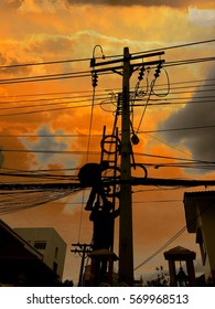 Silhouette of electricity working with wires at sunset background.