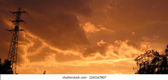 Silhouette of an eletric pylon and its cables against a mandarine cloudy sky at sunset