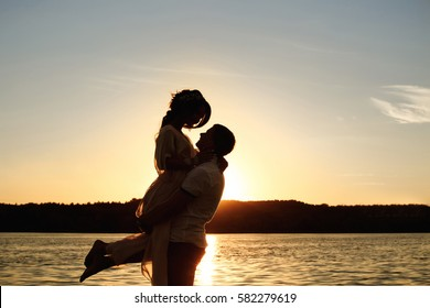 Silhouette of embracing couple near sea or ocean on sunset. Honeymoon.