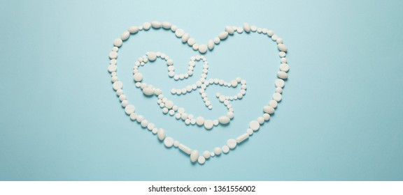 Silhouette of the embryo (child) of people in the heart of white tablets on blue background. Treatment of newborns, medical care.