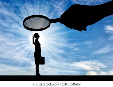 Silhouette of an employee woman. A hand with a magnifier over a woman. The concept of gender inequality and prejudice against women workers