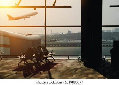 silhouette of empty airport terminal with airplane on background.