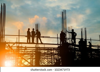 Silhouette of engineer and construction team working at site over blurred background sunset pastel for industry background with Light fair.