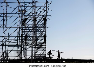 Silhouette of engineer and construction team working at site over sky background, construction concept