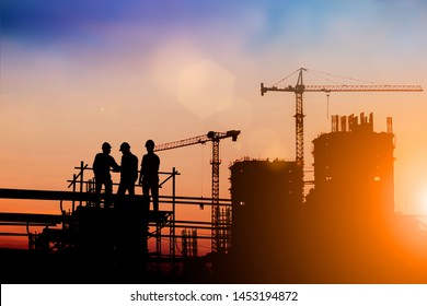 Silhouette of engineer and construction team working at site over blurred background for industry background with Light fair.