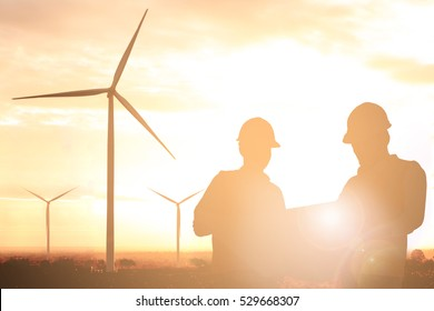 Silhouette of engineer and foreman at wind turbine electricity in sunset