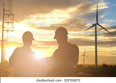 Silhouette of engineer and foreman at wind turbine electricity industrial in sunset