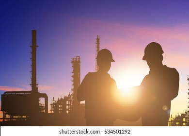Silhouette of engineer and foreman working at petrochemical oil refinery in sunrise