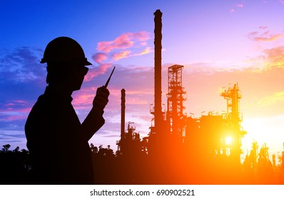 Silhouette of engineer and foreman working at petrochemical oil refinery in sunset