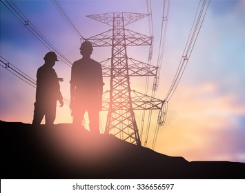 silhouette engineer looking  a building site over Blurred  high voltage transmission towers.