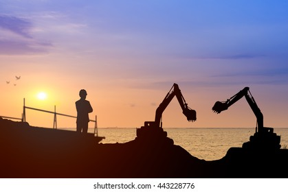 Silhouette engineer looking construction worker nearly sea beach with sunset background in a building site.Over Blurred construction worker on construction site nearly sea beach with sunset background