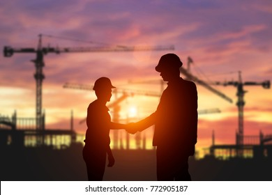 Silhouette of Engineer shakes hands In the construction area. Business Collaboration Concepts