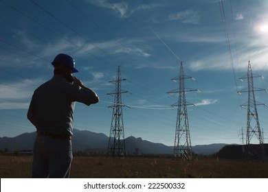 silhouette of engineer standing on field with electricity towers, talking on the phone