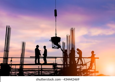 Silhouette engineer standing orders for construction crews to work safely on high ground  heavy industry and safety at work concept over blurred natural background sunset pastel.