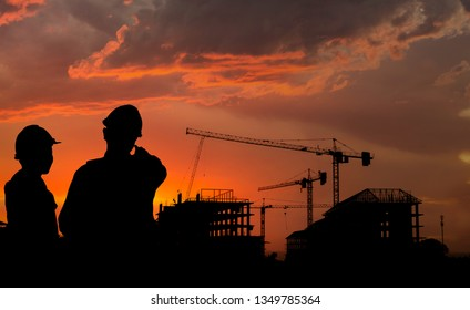 Silhouette engineer standing survey work on construction over blurred Worker in  construction site and sunset.