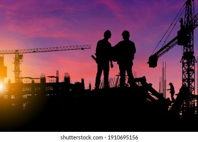 Silhouette of Engineer and worker checking project at building site background, construction site at sunset in evening time
