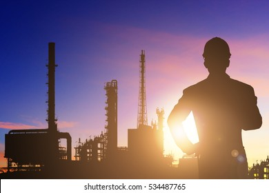 Silhouette of engineer working at petrochemical oil refinery in sunrise
