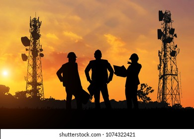 Silhouette of the engineers look at the telecommunication poles planned to be built at sunset time.