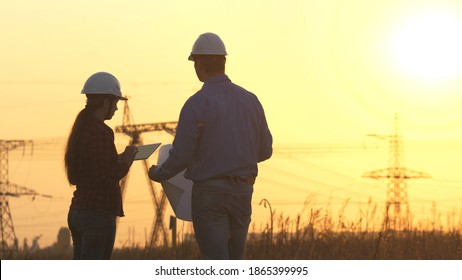 Silhouette of engineers looks at the construction of high-voltage power. Teams engineer looking discussing plan. Two engineer standing on field with electricity towers at sunset