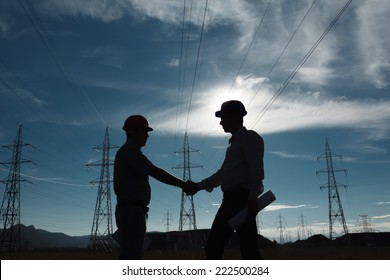 silhouette of engineers standing at electricity station shaking hands