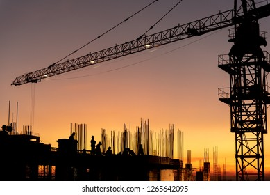 Silhouette Engineers and workers with Crane construction and team working in site. construction safety concept  background sunset