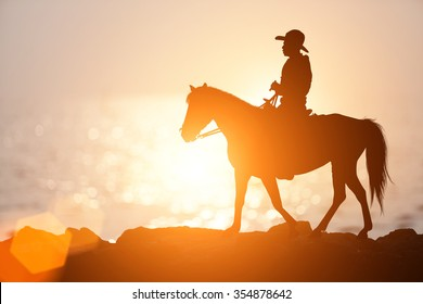 silhouette equestrian riding a horse on sunset background