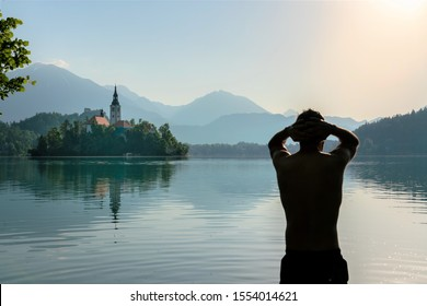 Silhouette of an European man doing morning stretches after practicing the method of meditation and deep breathing Wim Hof , while bathing in lake Bled.